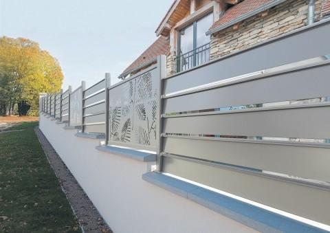 Panneaux brise vue aluminium Alujour, lames ajourées, personnalisés de panneaux découpe laser modèle Fougère, pose en redan sur muret avec couvertine béton