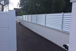 Claustra aluminium blanc ALUCLOS avec un portail aluminium coulissant.